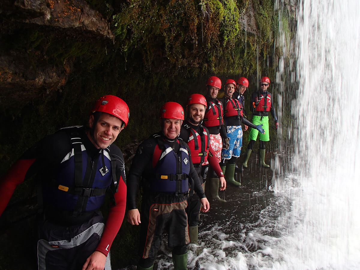 Happy faces under a waterfall while canyoning