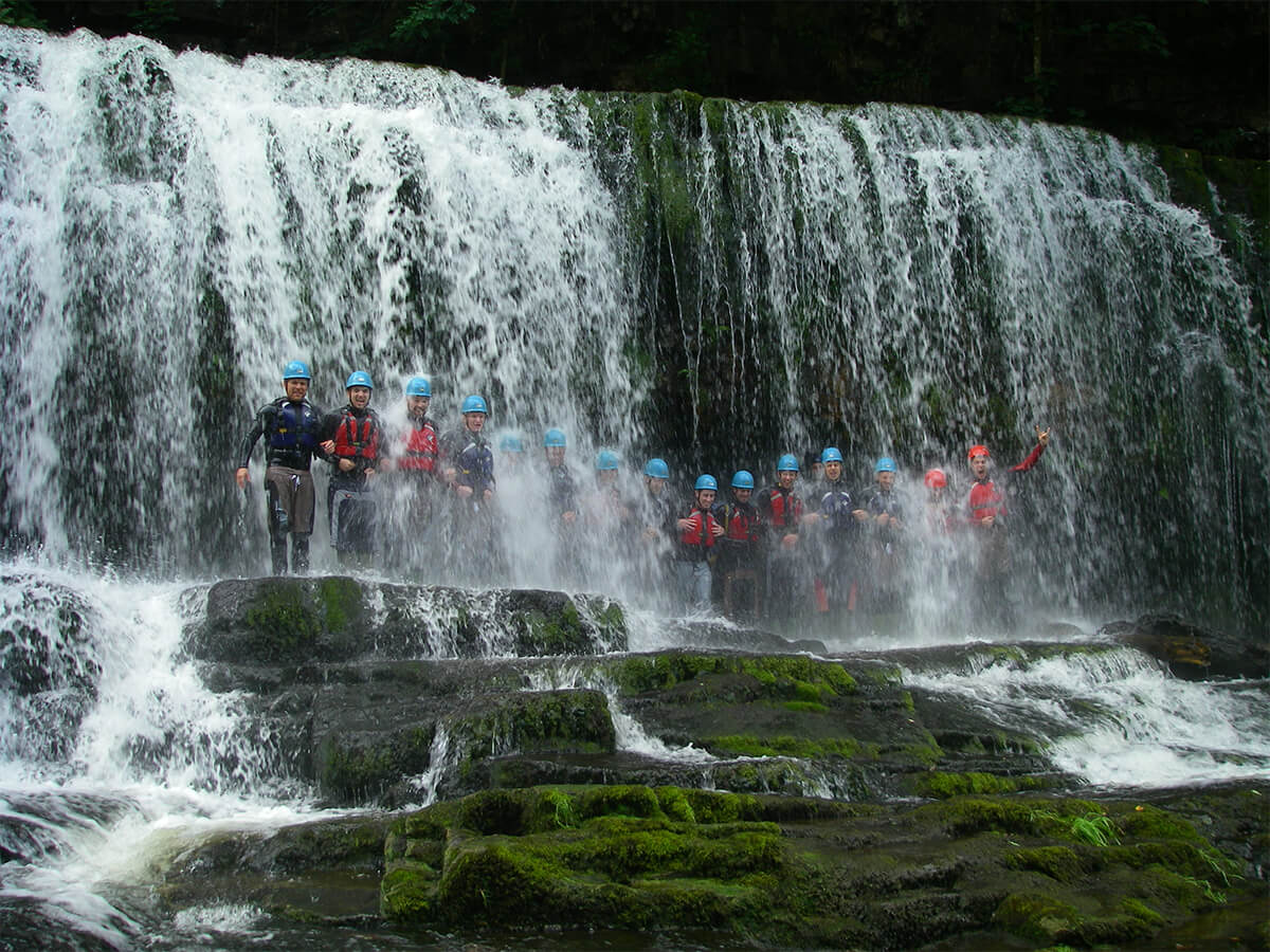 Large group having a group photo under a waterfall