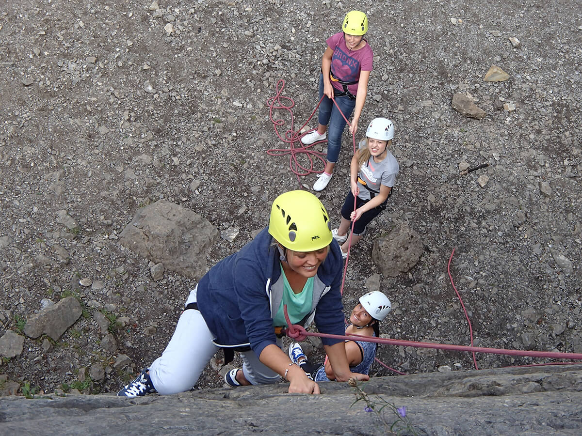 Group of happy ladies rock climbing