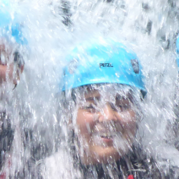 Three people under a waterfall